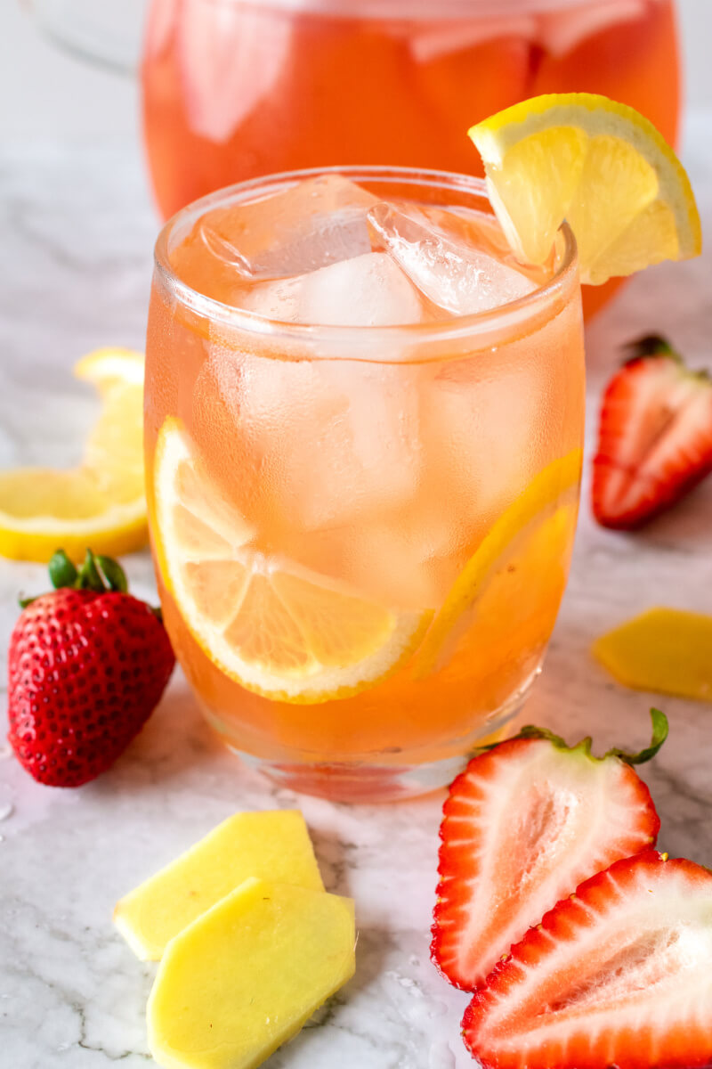 Glass filled with ice, lemon slices and a strawberry drink, sitting next to a glass pitcher filled with the drink and fresh strawberries, fresh sliced ginger and lemon slices.