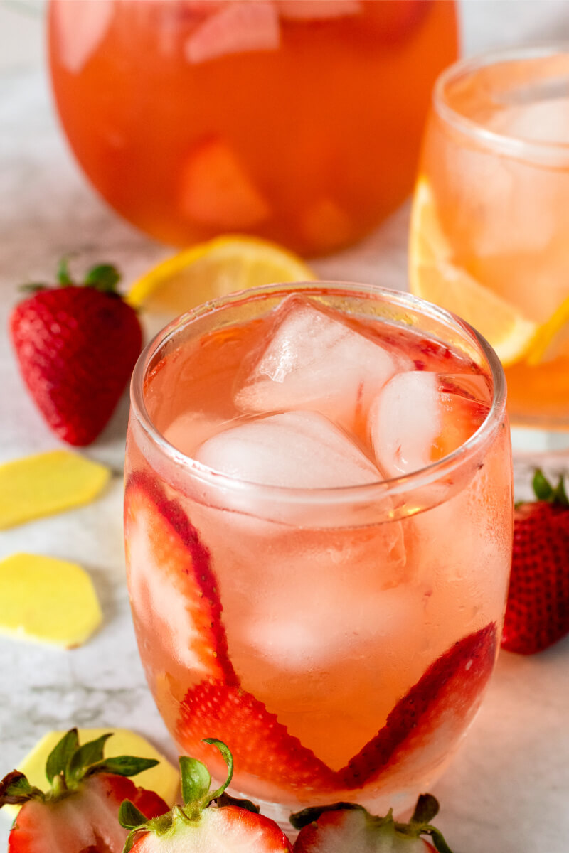 Glasses filled with ice, strawberry slices, lemon slices and a strawberry drink, sitting next to a glass pitcher filled with the strawberry drink and fresh strawberries, fresh sliced ginger and lemon slices.