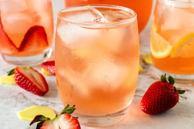 Glasses filled with ice, lemon slices, strawberry slices and a strawberry drink, sitting next to a glass pitcher filled with the drink and fresh strawberries, fresh sliced ginger and lemon slices.