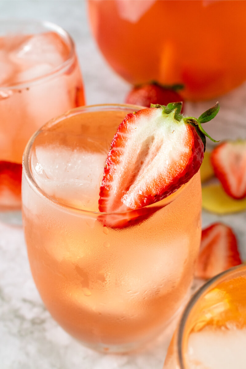 Glasses filled with ice, strawberry slices and a strawberry drink, sitting next to a glass pitcher filled with the drink, fresh strawberries and fresh sliced ginger.
