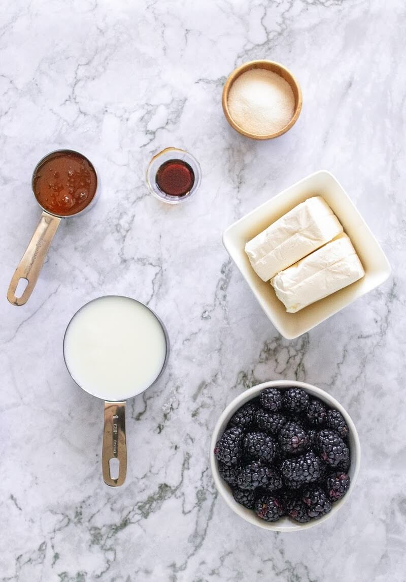 Fresh blackberries, cream cheese, vanilla extract, honey, milk and collagen ingredients displayed in measuring cups and bowls.