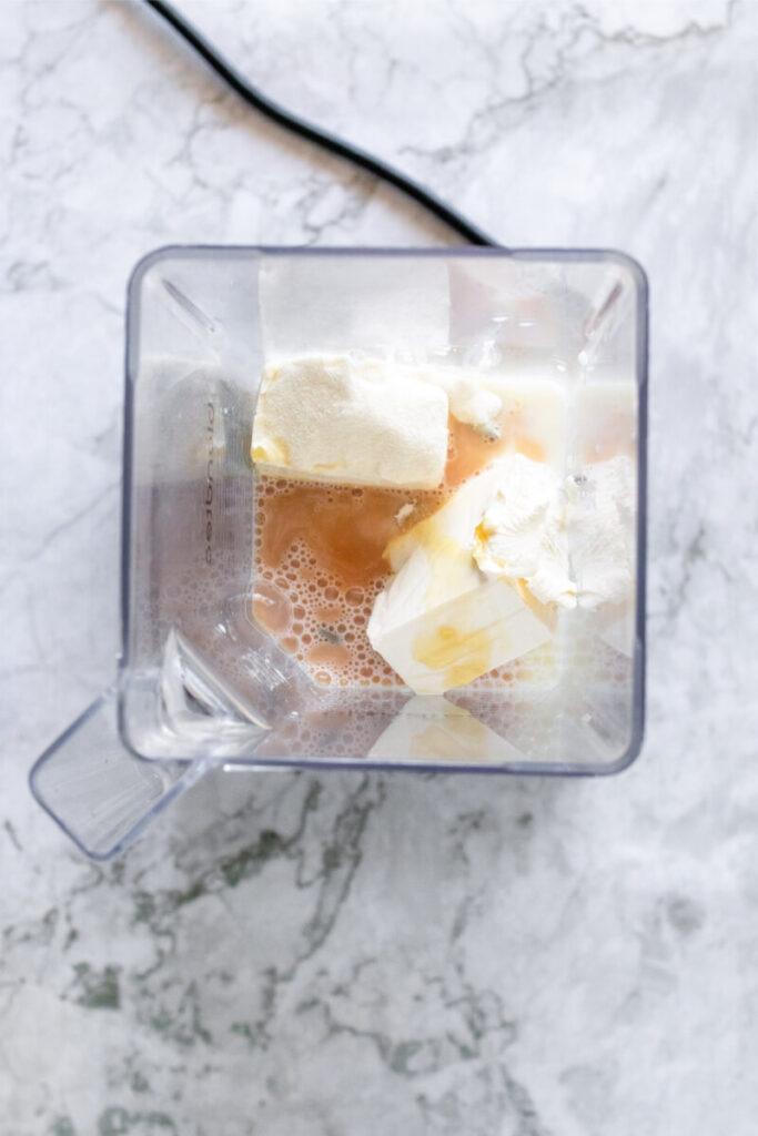 Blender filled with cream cheese, milk and vanilla extract.