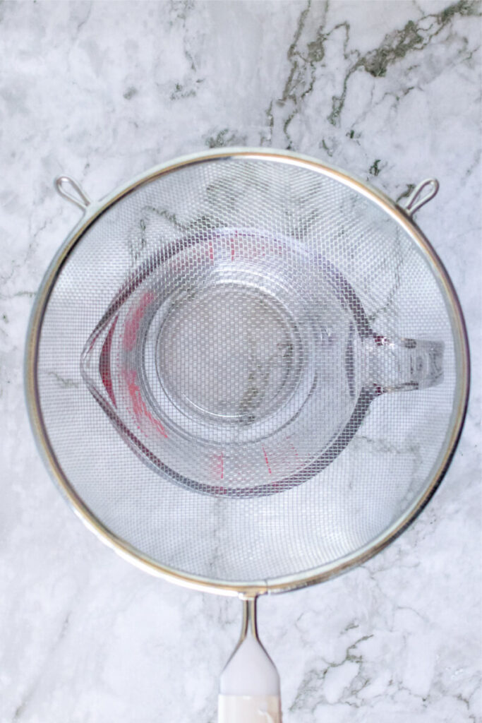 Fine mesh strainer sitting on top of a measuring cup.