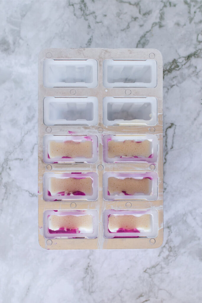 Homemade popsicles being filled and assembled in a 10-count popsicle mold.