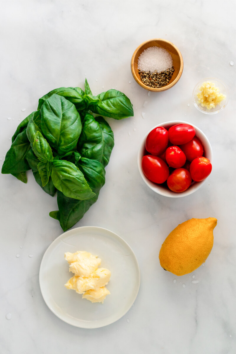 Fresh basil, bowl of fresh cherry tomatoes, lemon, plate with fresh butter, small bowl of minced garlic and small bowl of salt and pepper.