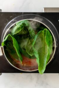 Overhead view of saucepan cooking homemade tomato sauce with fresh basil.