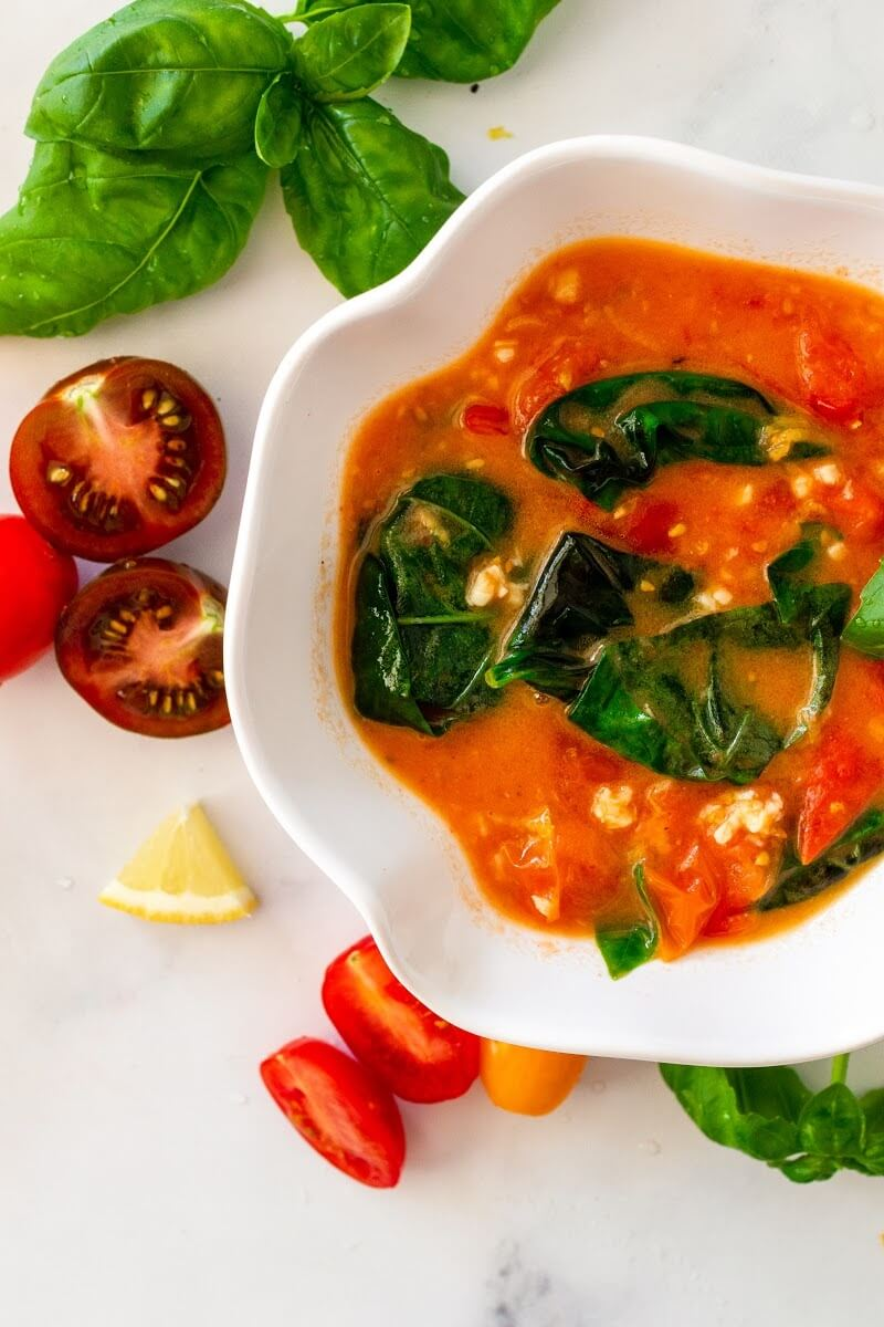 Bowl full of homemade tomato basil sauce surrounded by fresh cherry tomatoes, fresh basil and lemon slices.
