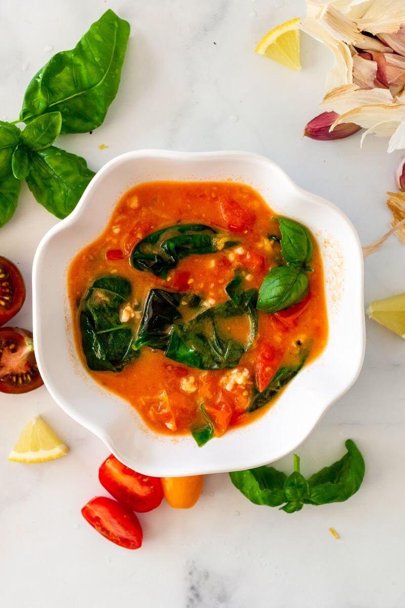 Bowl full of homemade tomato basil sauce surrounded by fresh cherry tomatoes, fresh basil, lemon slices and fresh garlic cloves.