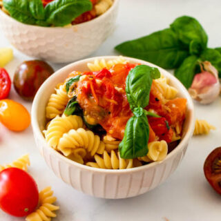 Two bowls full of pasta topped with homemade tomato basil sauce with a sprig of fresh basil, surrounded by fresh cherry tomatoes, fresh basil, lemon slices and fresh garlic clove.