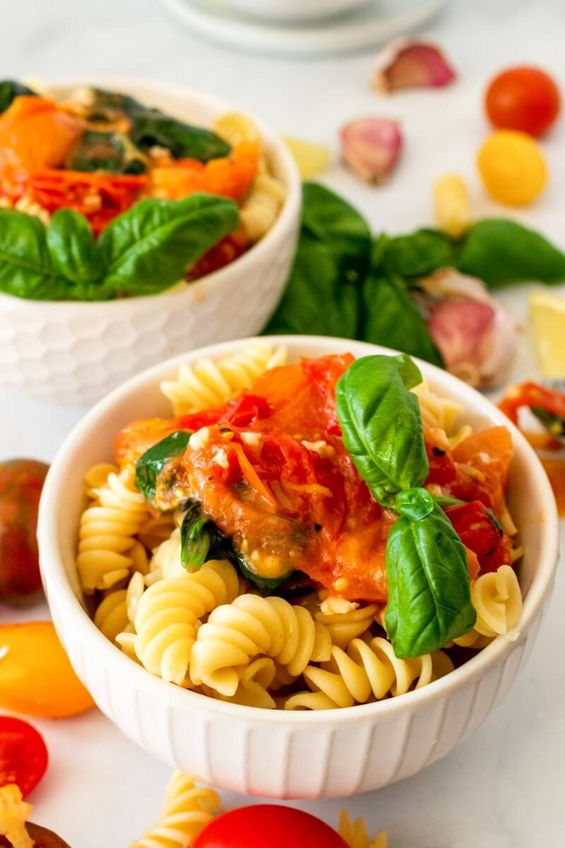 Two bowls full of pasta topped with homemade tomato basil sauce with a sprig of fresh basil, surrounded by fresh cherry tomatoes and fresh basil.