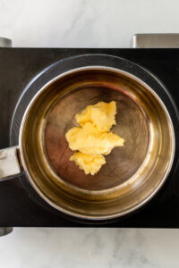 Overhead view of butter in a saucepan.