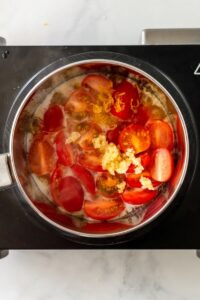 Overhead view of saucepan cooking homemade tomato sauce with fresh cherry tomatoes and fresh chopped garlic.