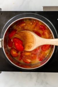 Overhead view of saucepan cooking homemade tomato sauce with fresh cherry tomatoes being stirred with a wooden spoon.
