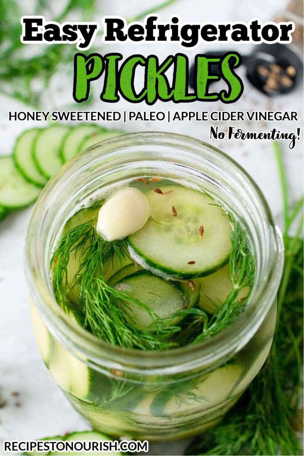 Mason jar filled with sliced pickles, fresh dill, garlic clove and liquid brine, surrounded by sliced cucumbers, fresh dill, spices and the text Easy Refrigerator Pickles.