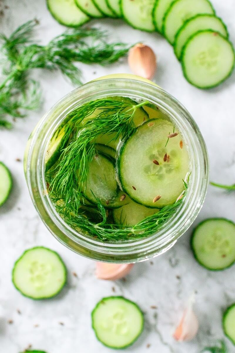 Mason jar filled with sliced pickles, fresh dill and liquid brine, surrounded by sliced cucumbers, fresh dill, garlic cloves and spices.