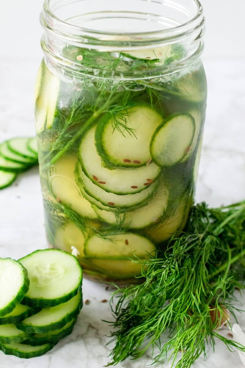 Mason jar filled with sliced pickles, fresh dill and liquid brine, surrounded by sliced cucumbers, fresh dill and spices.