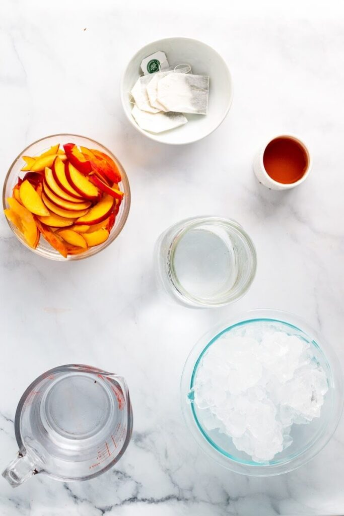 Overhead photo of a bowl full of ice, a glass measuring cup full of water, a jar full of water, a bowl full of sliced peaches, a small bowl of honey and a small bowl with tea bags in it.