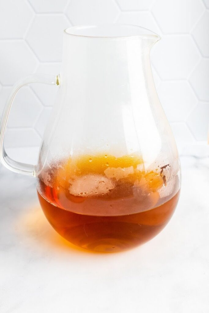 A glass pitcher 1/4 full of hot steamy tea.