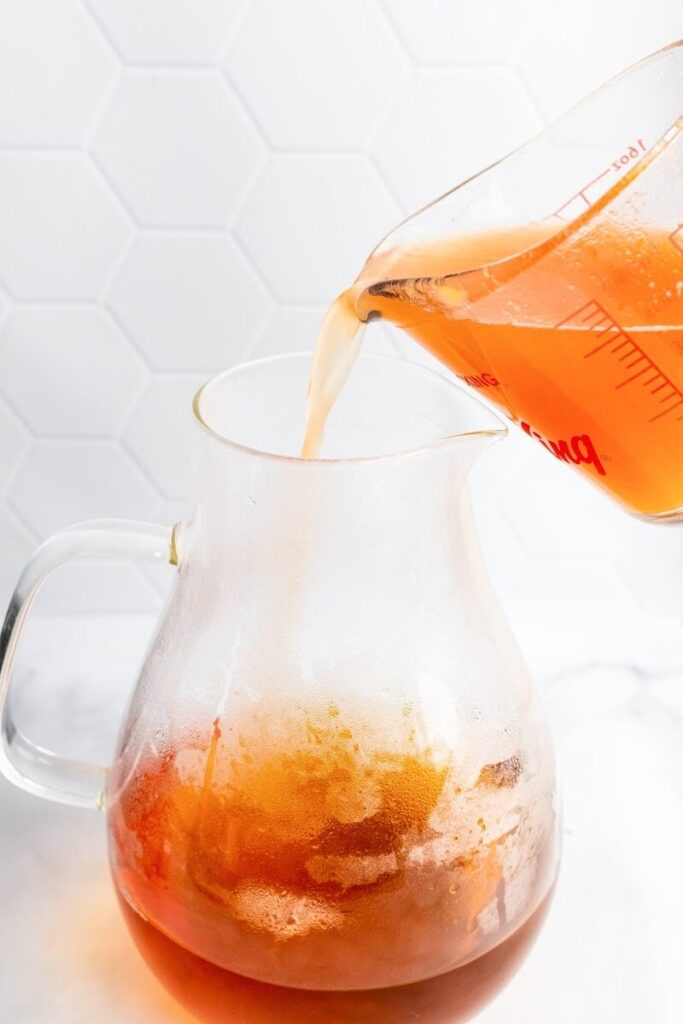 A glass measuring cup pouring peach liquid into a glass pitcher half full with tea.