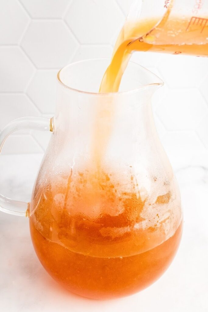 A glass measuring cup pouring peach liquid into a glass pitcher half full with peach tea.