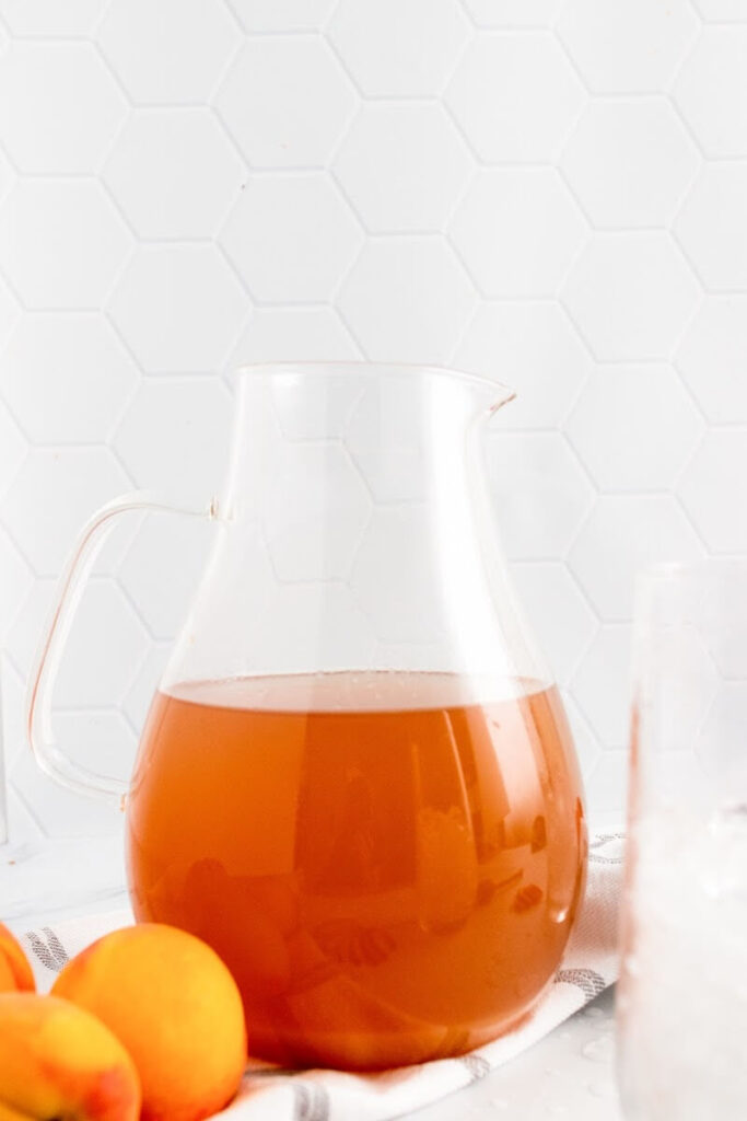 A glass pitcher half full with peach tea sitting next to fresh peaches and a glass filled with ice.