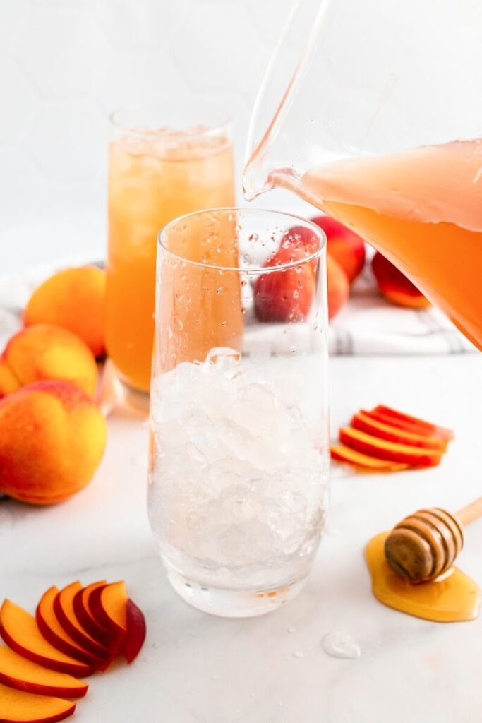 A glass half full with ice and a glass pitcher filled with peach tea about to pour into the glass, sitting next to sliced peaches, fresh whole peaches, a honey dipper and a glass full of iced peach tea.