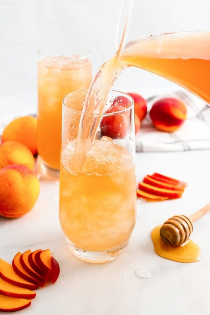 A glass half full with iced peach tea and a glass pitcher filled with peach tea pouring into the glass, sitting next to sliced peaches, fresh whole peaches, a honey dipper and a glass full of iced peach tea.