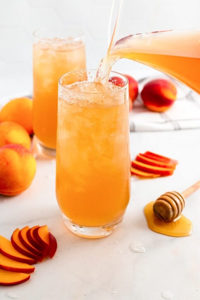 A glass full with iced peach tea and a glass pitcher filled with peach tea pouring into the glass, sitting next to sliced peaches, fresh whole peaches, a honey dipper and a glass full of iced peach tea.