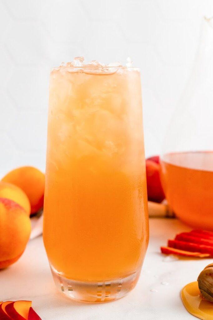 A glass full of iced peach tea sitting next to sliced peaches, fresh whole peaches, a honey dipper and a pitcher half full of peach tea.