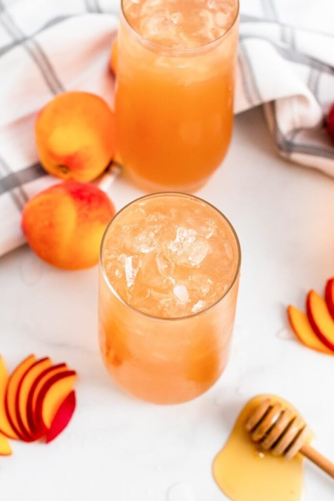 An overhead view of two glasses full of iced peach tea sitting next to sliced peaches, fresh whole peaches and a honey dipper.