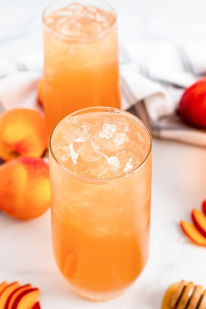 Two glasses full of iced peach tea sitting next to sliced peaches, fresh whole peaches and a honey dipper.