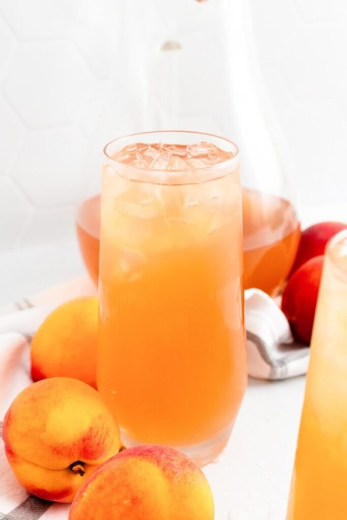 A glass full of iced peach tea sitting next to fresh whole peaches and a pitcher half full of peach tea.