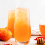 Two glasses full of iced peach tea sitting next to sliced peaches, fresh whole peaches, a honey dipper and a pitcher half full of peach tea.