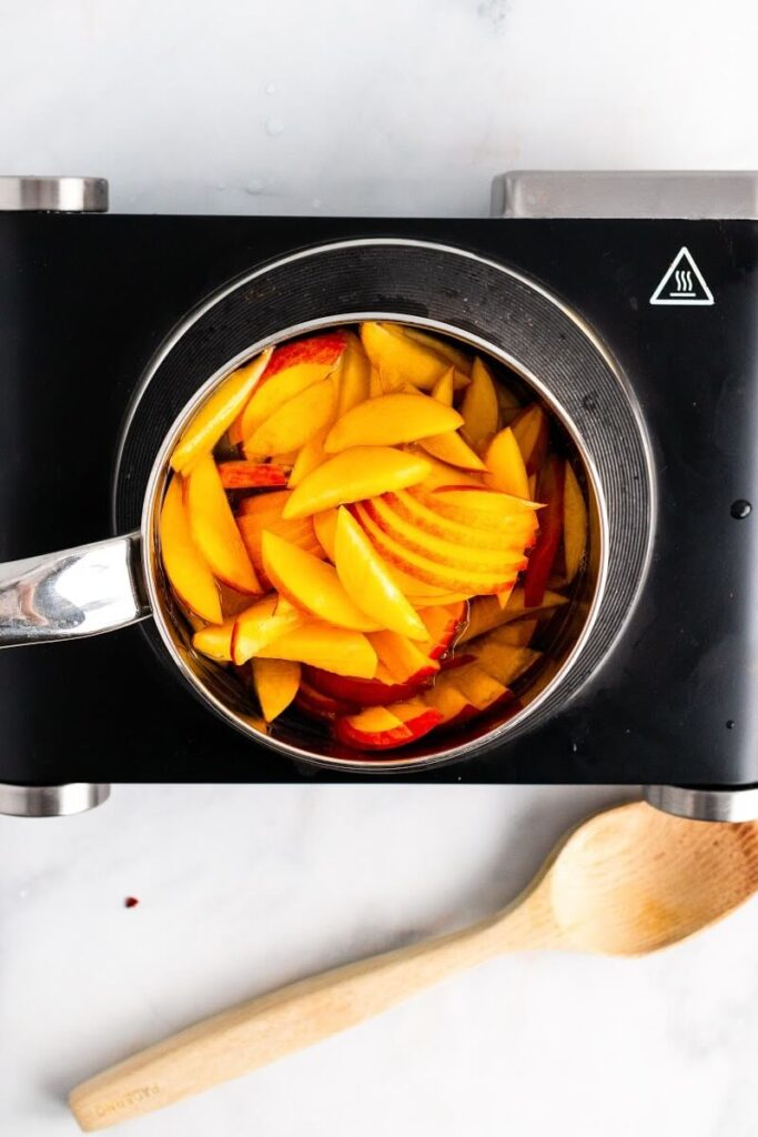 A saucepan full of sliced peaches sitting on top of an electric stovetop with a wooden spoon next to it.