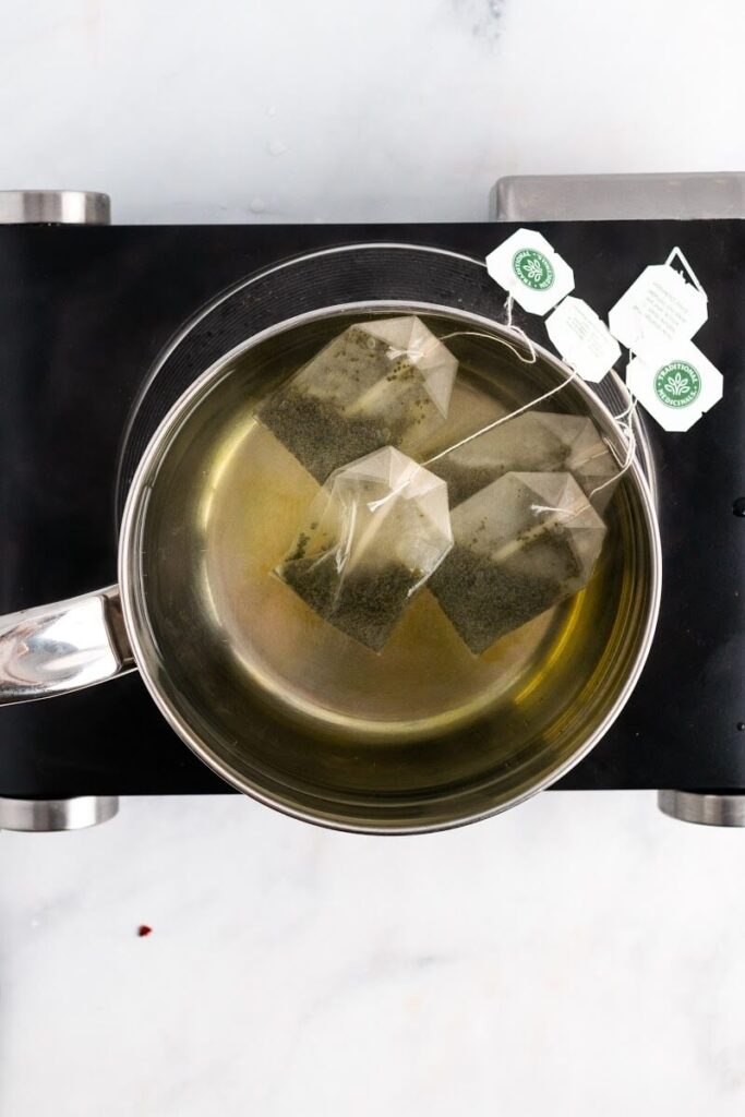 A saucepan with water and 4 tea bags steeping in it sitting on top of an electric stovetop.