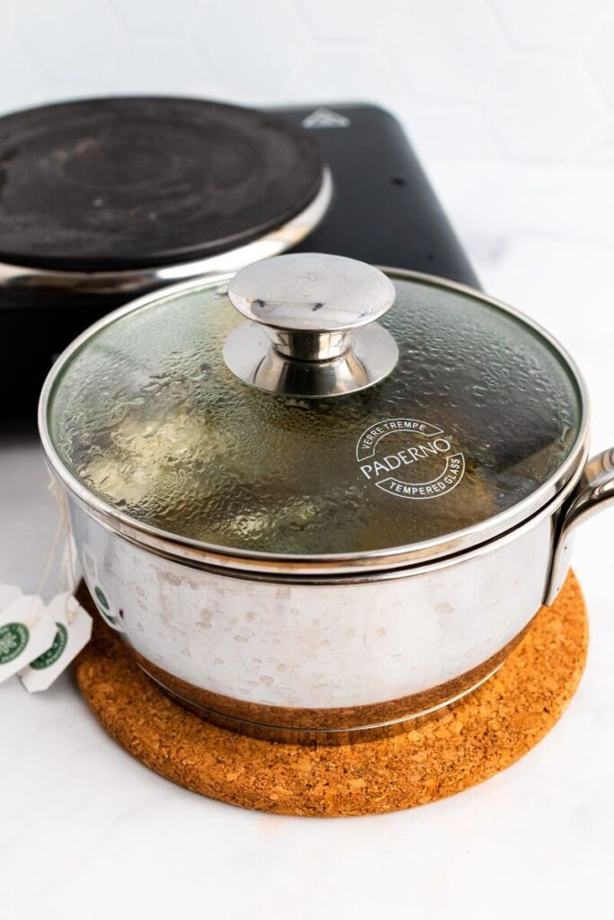 A hot saucepan covered with a steamed up glass lid with tea bag strings hanging out the side of it sitting next to an electric stovetop.