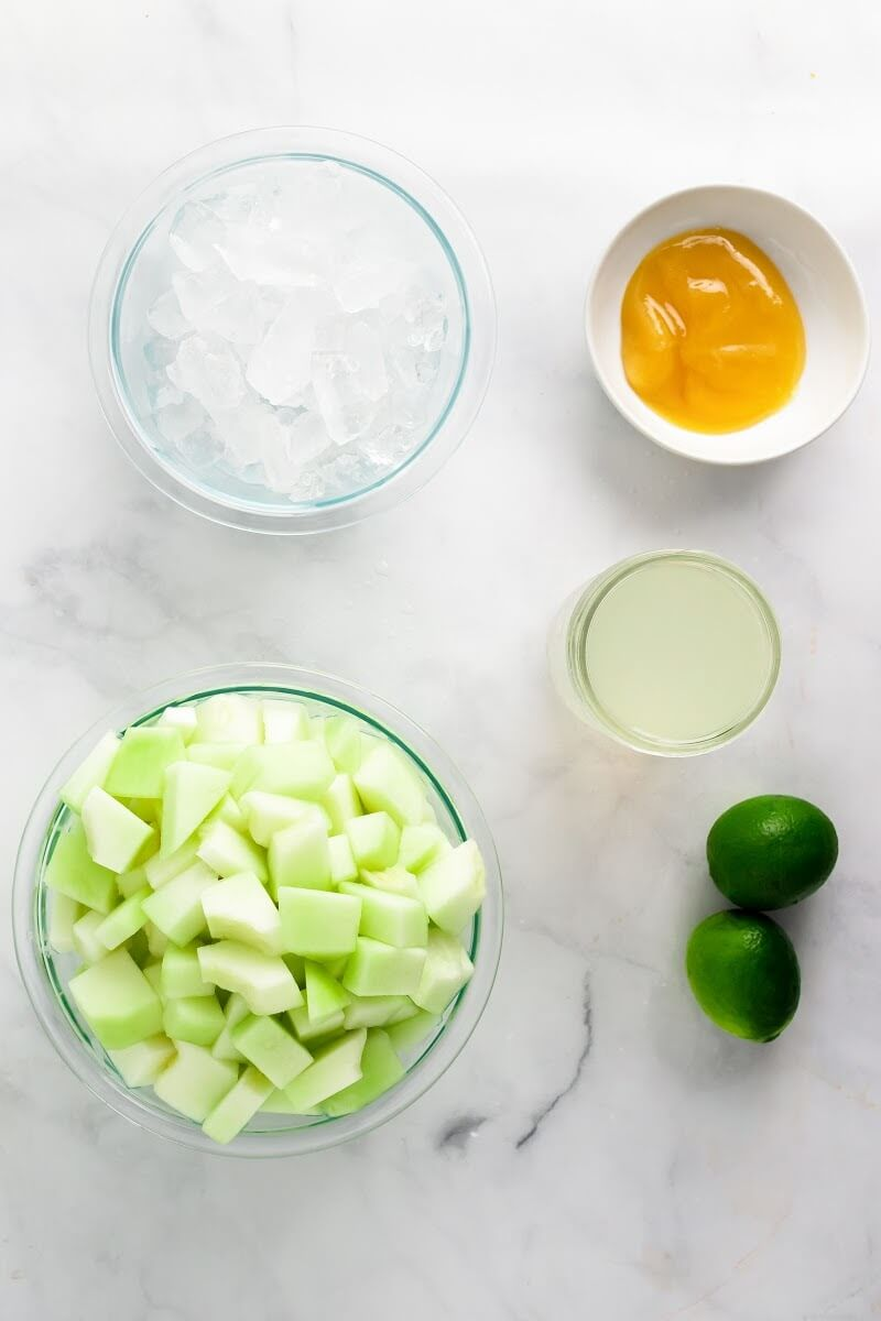 An overhead view of ingredients with a bowl full of honeydew melon chunks, a bowl filled with ice, a small bowl filled with honey, a jar full of coconut water and two limes.