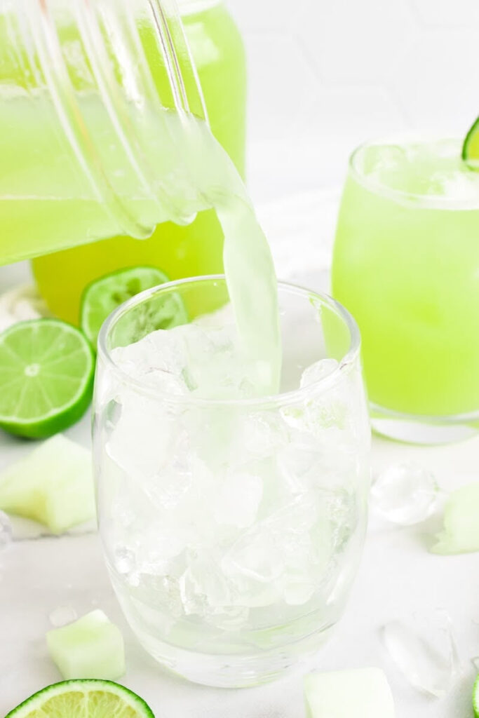 Green-colored drink being poured into a glass filled with ice, next to another glass full of the iced green drink with a slice of fresh lime on the rim, surrounded by chunks of honeydew melon, ice cubes, fresh lime slices and a jar filled with the drink.