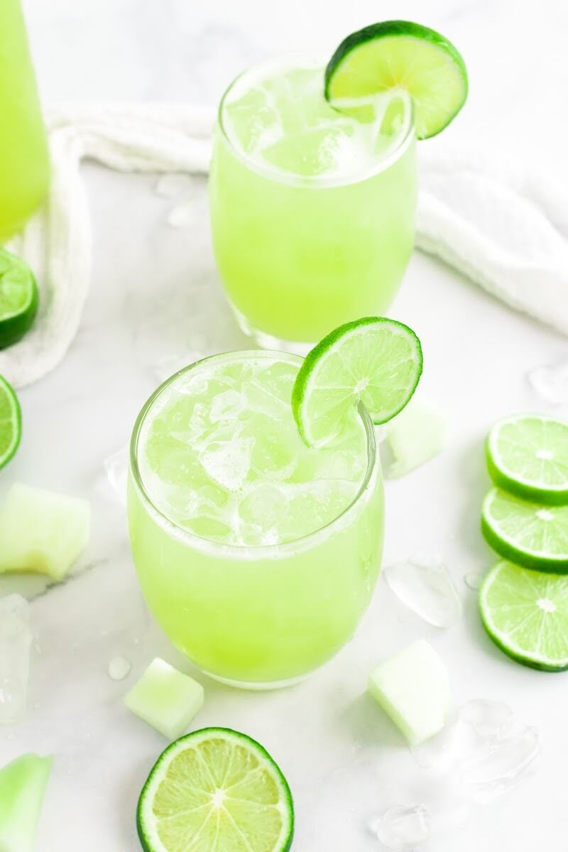 Two glasses filled with iced green-colored drink with a slice of fresh lime on the rim, surrounded by chunks of honeydew melon, fresh lime slices and a jar filled with the drink.