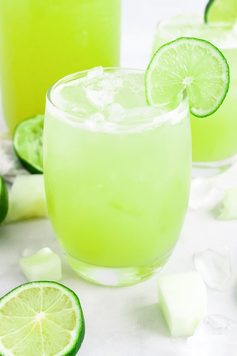 Two glasses filled with iced green-colored drink with a slice of fresh lime on the rim, surrounded by chunks of honeydew, fresh lime slices and a jar filled with the drink.