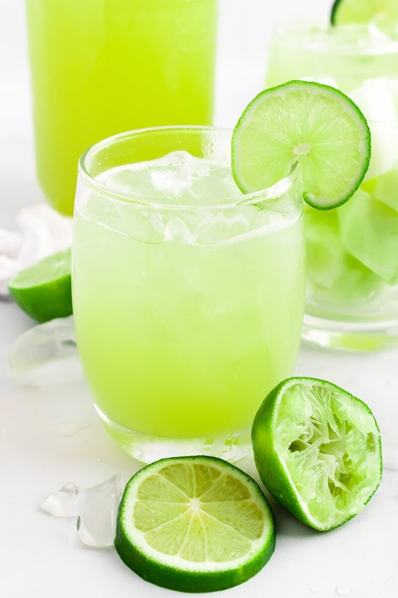 Glass filled with iced green-colored drink with a slice of fresh lime on the rim, surrounded by chunks of honeydew melon in a glass, ice cubes, fresh lime slices and a jar filled with the drink.
