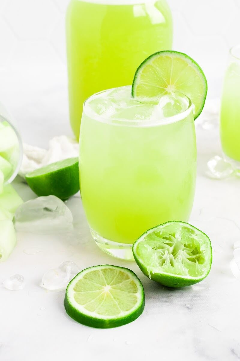 Glass filled with iced green-colored drink with a slice of fresh lime on the rim, surrounded by chunks of honeydew melon, ice cubes, fresh lime slices and a jar filled with the drink.