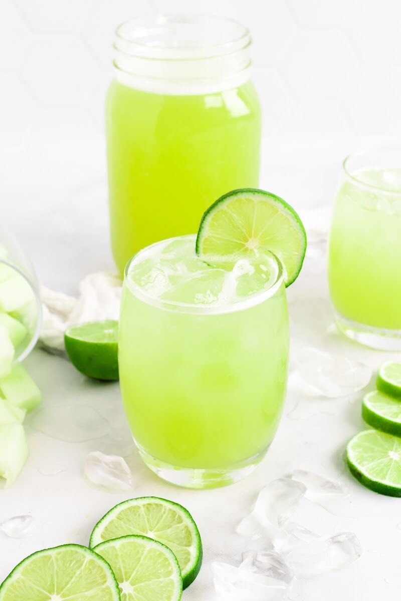 Glass filled with iced green-colored drink with a slice of fresh lime on the rim, surrounded by chunks of honeydew melon, ice cubes, fresh lime slices, another glass filled with the iced green drink and a jar filled with the drink.