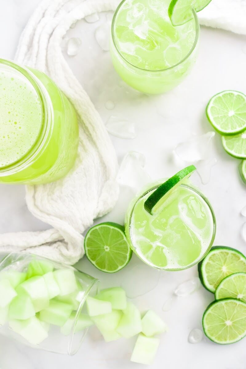 Overhead view of two glasses filled with iced green-colored drink with a slice of fresh lime on the rim, surrounded by chunks of honeydew melon, fresh lime slices and a jar filled with the drink.