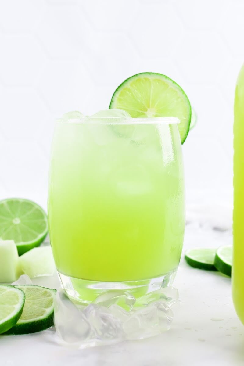 Glass filled with iced green-colored drink with a slice of fresh lime on the rim, surrounded by chunks of honeydew, fresh lime slices and a jar of the drink to the side.