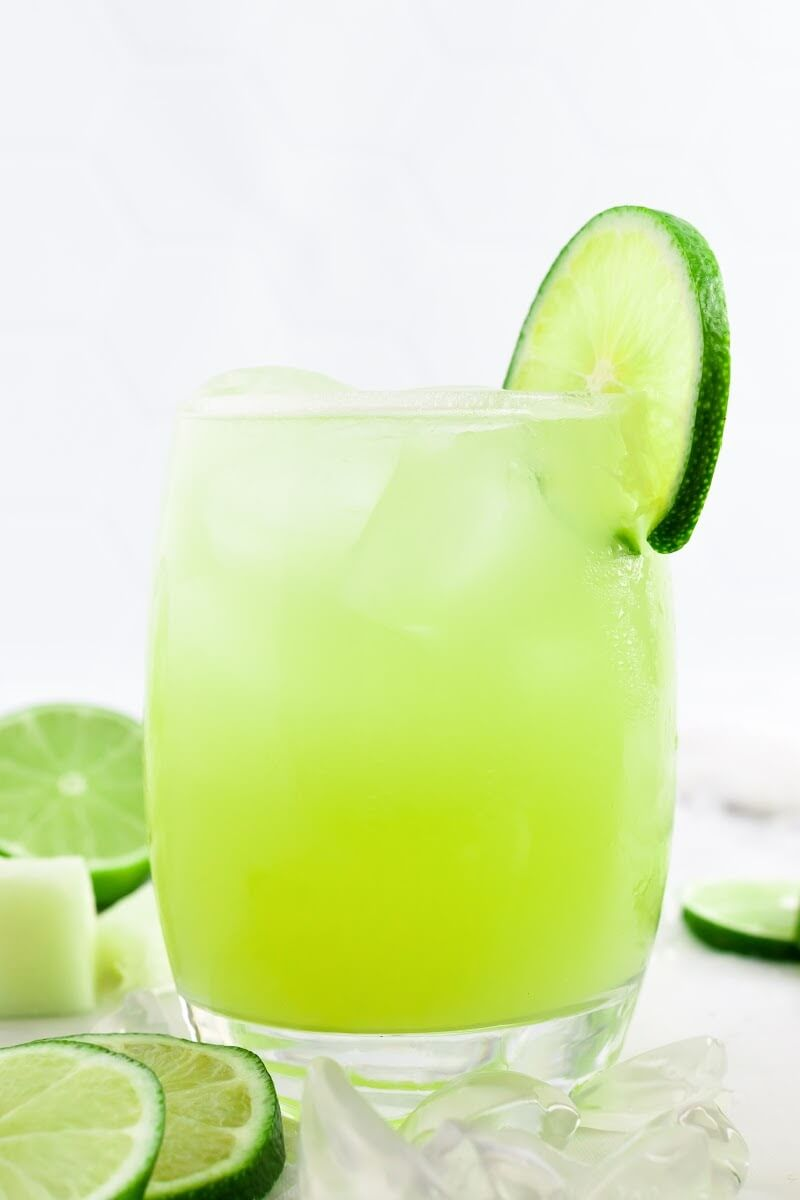 Glass filled with iced green-colored drink with a slice of fresh lime on the rim, surrounded by chunks of honeydew and fresh lime slices.