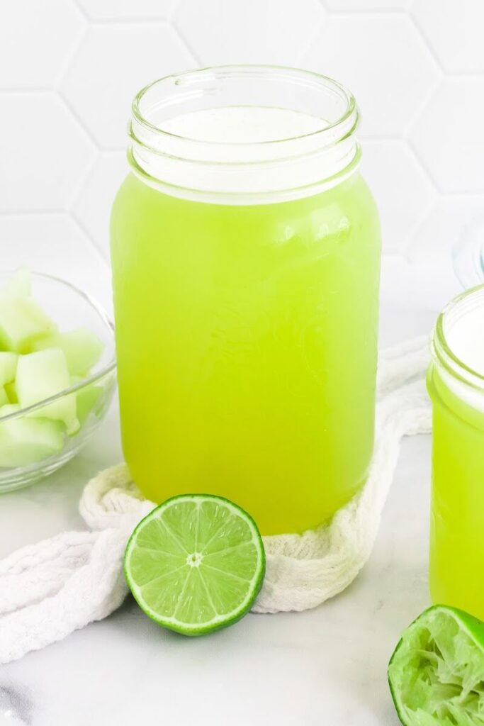 Two mason jars filled with a green-colored drink sitting next to a bowl with chunks of honeydew melon, a half of a juiced lime and a half of a fresh lime.