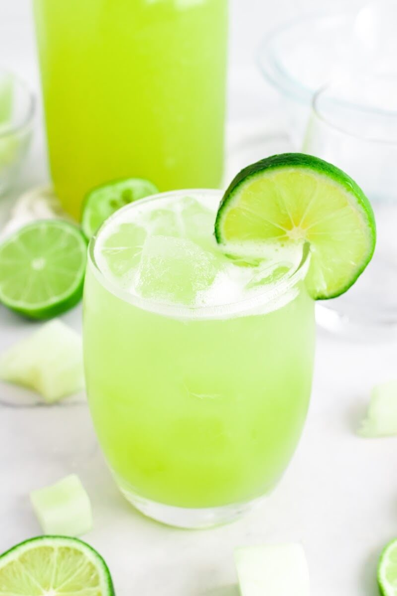 Glass filled with iced green-colored drink with a slice of fresh lime on the rim, surrounded by chunks of honeydew, fresh lime slices and a jar filled with the drink.