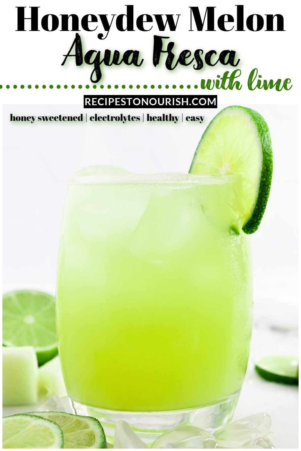 Glass filled with iced green-colored drink with a slice of fresh lime on the rim, surrounded by chunks of honeydew and fresh lime slices and the text Honeydew Melon Agua Fresca with Lime.