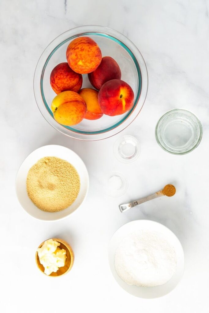 Overhead view of the following ingredients: a bowl full of fresh peaches, a small bowl full of maple sugar, a small bowl of cassava flour, a tiny bowl with butter, a teaspoon with cinnamon powder, a glass of water and two tiny bowls of almond extract.